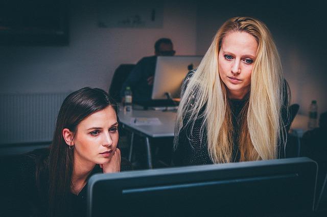 žena, které se dívají do počítače a cosi kontrolují nebo sledují